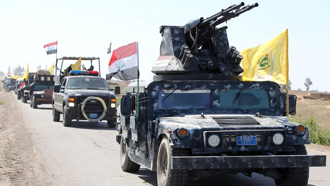 Members of the Iraqi security forces drive toward al-Dawr, south of Tikrit, to launch an assault against the Islamic State.