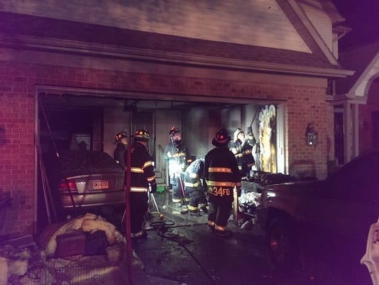 Firefighters investigate a garage wall during a fire at a home in Windsor Township.