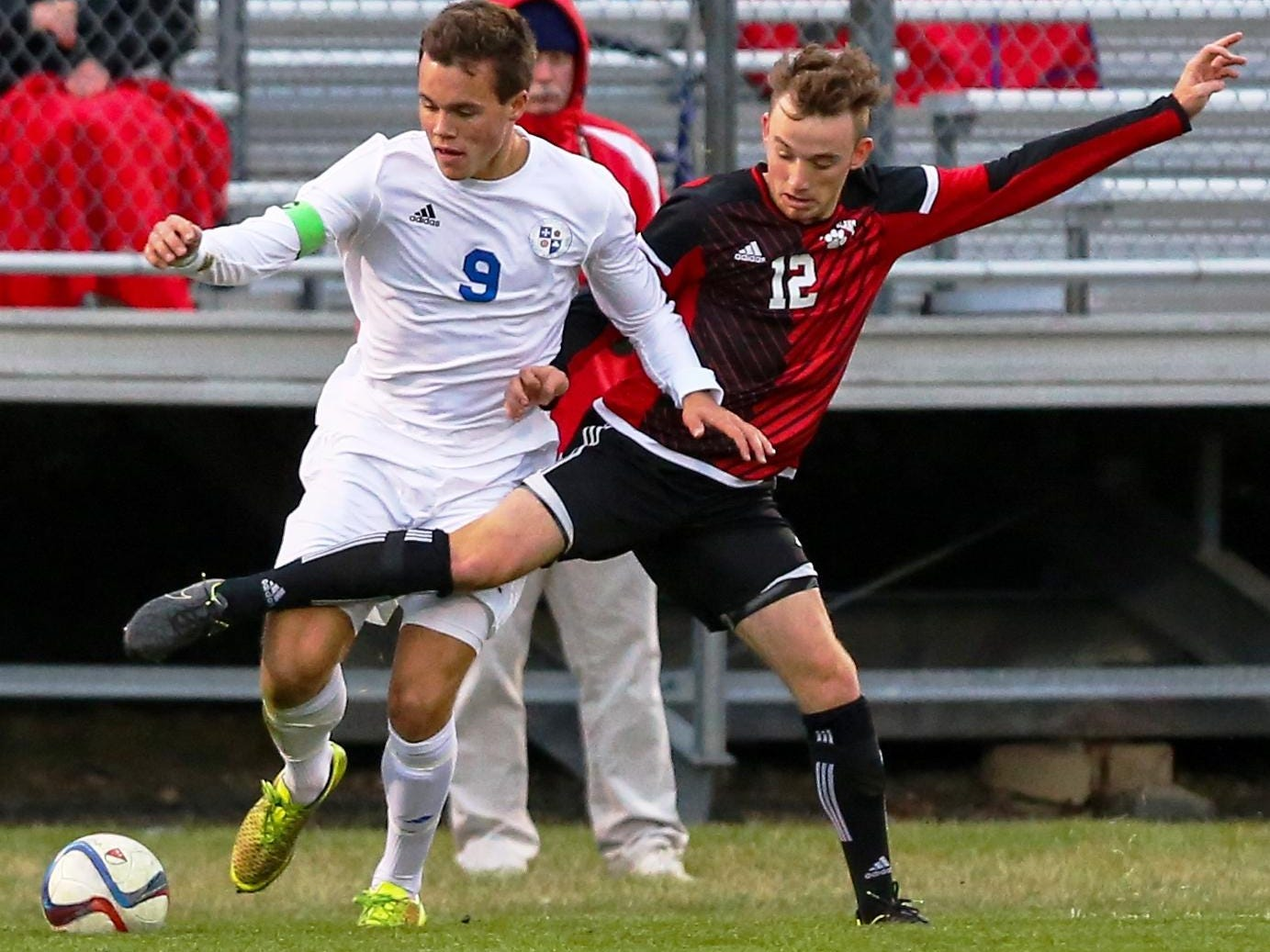 Catholic Central's Justin Murray (left) tries to fend off Grand Blanc's Dayton Rush.