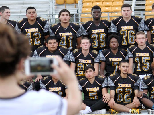 "The Alamogordo Tigers football team prepares to take a team photo during ""Media Day"" on Friday evening."