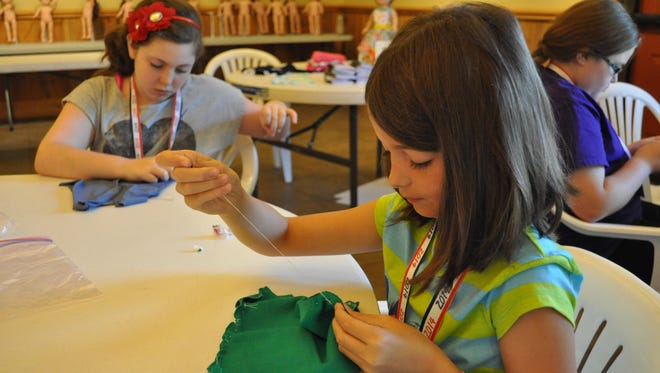 Ellianna Blackwell sews an outfit for her doll during Jane in June camp, held Tuesday at the Kent Plantation House.