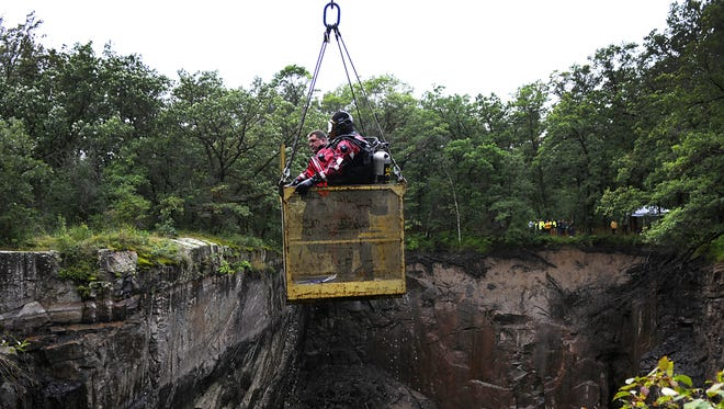 Stearns-Benton County divers Dave Bonfineld and David Patterson are lifted up from Quarry 8 on Aug. 19 at Quarry Park & Nature Preserve after conducting a search of the quarry.
