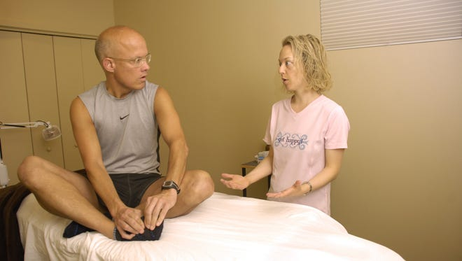 Abby Miller, acupuncturist with the Des Moines Acupuncture Clinic, chats with marathon runner Daniel Garrett inside the Des Moines clinic.