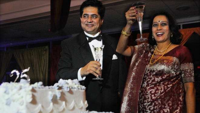 Anjan and wife Reena Ghosal drink a toast as they celebrate their 25th wedding anniversary Sunday evening at the Cocoa Civic Center.
