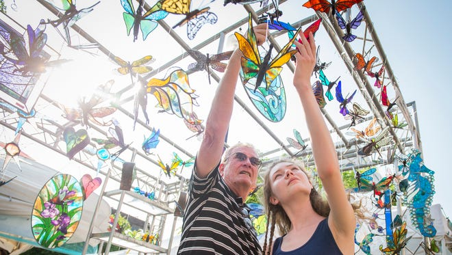 Festival goers browse the art at the Debi Dwyer Design booth at the Dogwood Arts Festival held in downtown Knoxville on Friday, April 28, 2017.