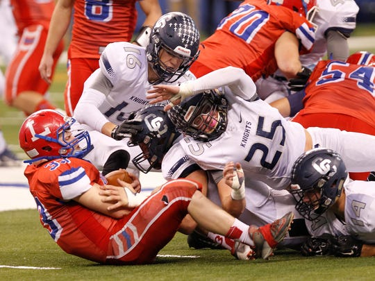 The Central Catholic defense stops Garrett Mason of Linton-Stockton in the Class A state finals Friday, November 27, 2015, at Lucas Oil Stadium in Indianapolis. Central Catholic defeated Linton-Stockton 34-7.