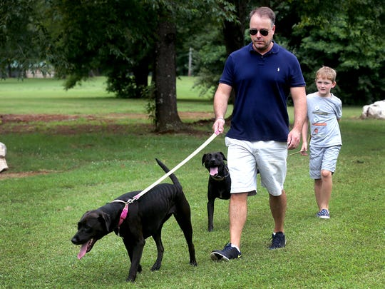 Brice Jennings walks Ruby as Hayden Fry, 8, walks Janet, at the site of the new dog park, Bark Springs at Sharp Springs.