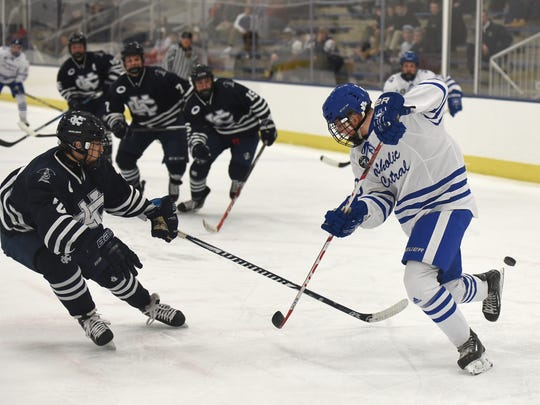 Catholic Central Shamrock Carter Korpi tries to corale a pass that's slipped behind his skates as Cranbrook's Blake Salesin bears down during the teams' Jan. 27 at USA Arena in Plymouth Township.