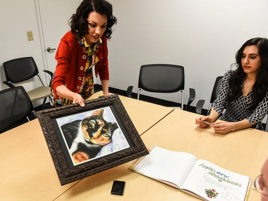 Olivia Moy shows a watercolor painting of her cat,