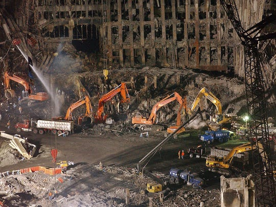 Workers and heavy machinery assist in the cleanup and recovery effort in front of the remaining facade of the World Trade Center in New York on Nov.7, 2001.