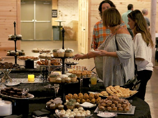 Several people browse through the desserts table during
