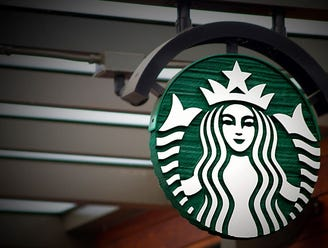 Starbucks mermaid sign hanging from a ceiling near a brick wall.