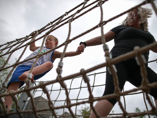 In this Tuesday, July 7, 2015 photo, Steven Heffron, 6, and his mother, Denise Watts, play in Smale Riverfront Park in downtown Cincinnati. Watts has filed a federal lawsuit alleging discrimination, saying an Ohio YMCA excluded her son from summer camp because he has Down syndrome and treated him hypocritically after using him in promotions extolling opportunities for everyone.