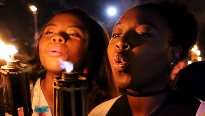 Midwestern State University students Marissa Norris , left, and Ashma Henry blow out their torches at the end of the Torchlight Parade Thursday, Oct. 19, 2017, at Midwestern State University.
