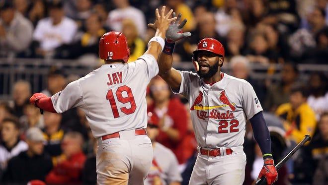 Cardinals right fielder Jason Heyward greets center fielder Jon Jay after Jay scored a run inthe seventh inning at PNC Park.