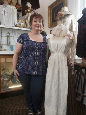 Kate Butler, owner of Decotique, a fine vintage apparel and antique store in Merchantville, stands by a turn-of-the-century cook's uniform she wears when portraying Typhoid Mary. Customers come to her shop for bridal wear, lingerie, hats and much more.