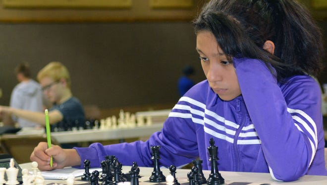 Roma Plansencia, 12, from El Paso writes down her moves during a chess tournament for kids hosted by Las Cruces Chess Academy on Oct. 8, 2016.