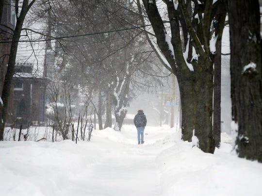 A pedestrian braves the cold and blowing snow Wednesday