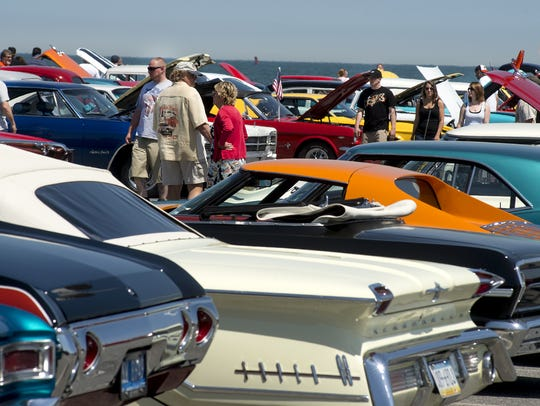 Car enthusiasts walk around Inlet Lot in Ocean City