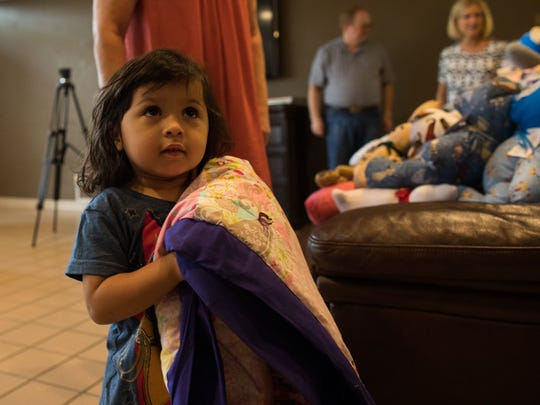 Oaklei Loera, 2, carries a quilt donated by the Order of the Eastern Star to the Ronald McDonald House Charities of Corpus Christi on Wednesday, July 12, 2017.