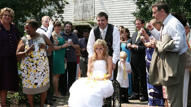 Rachelle Friedman, a bride paralyzed in 2010, and husband Chris Chapman, leave their wedding reception following a surprise vehicle donation from the Braun Corporation and Toyota Mobility on July 22, 2011, in Pittsboro, N.C.