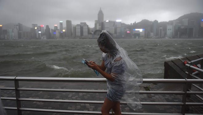 A woman uses her phone while wearing a plastic poncho along Victoria Harbour during heavy winds and rain brought on by Typhoon Hato in Hong Kong on Aug. 23, 2017.