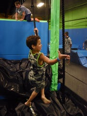 Giano Chervony, 8, of Newburgh clears the ropes inside the Extreme Zone obstacle course at BounceU in the Town of Poughkeepsie on Friday.