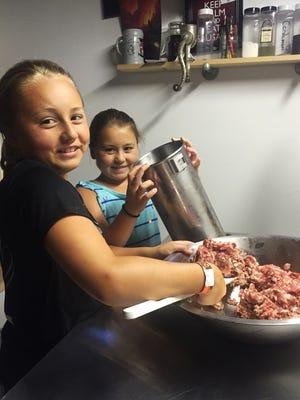 Stella (foreground) and Sophia Maciejewski work together on a batch of sausage.