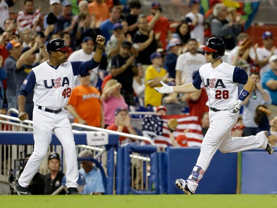 Team USA third base coach Willie Randolph (left) congratulating Buster Posey after he hit a home run against Canada at the World Baseball Classic.