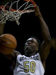 Vanderbilt center Ejike Obinna (50) hangs onto the rim after dunking.