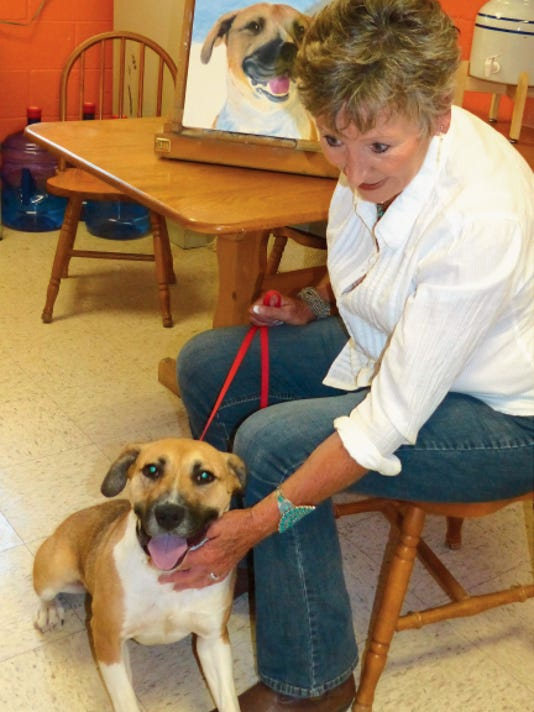 Artist Barb Yates pets Summer. a Labrador mix and the longest resident of the animal shelter on Gavilan Canyon Road. Behind Yates is the portrait in progress of Summer.