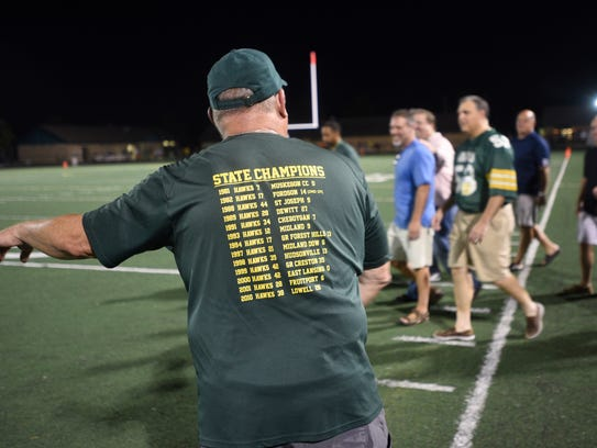 Former Harrison football players are lead onto the