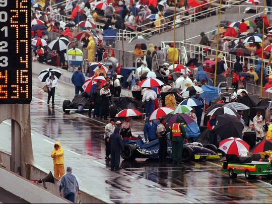 Crews push cars back to the garage area at the Indianapolis Motor Speedway, Monday, May 26, 1997. Rain stopped the Indy 500 after only 15 laps were completed.