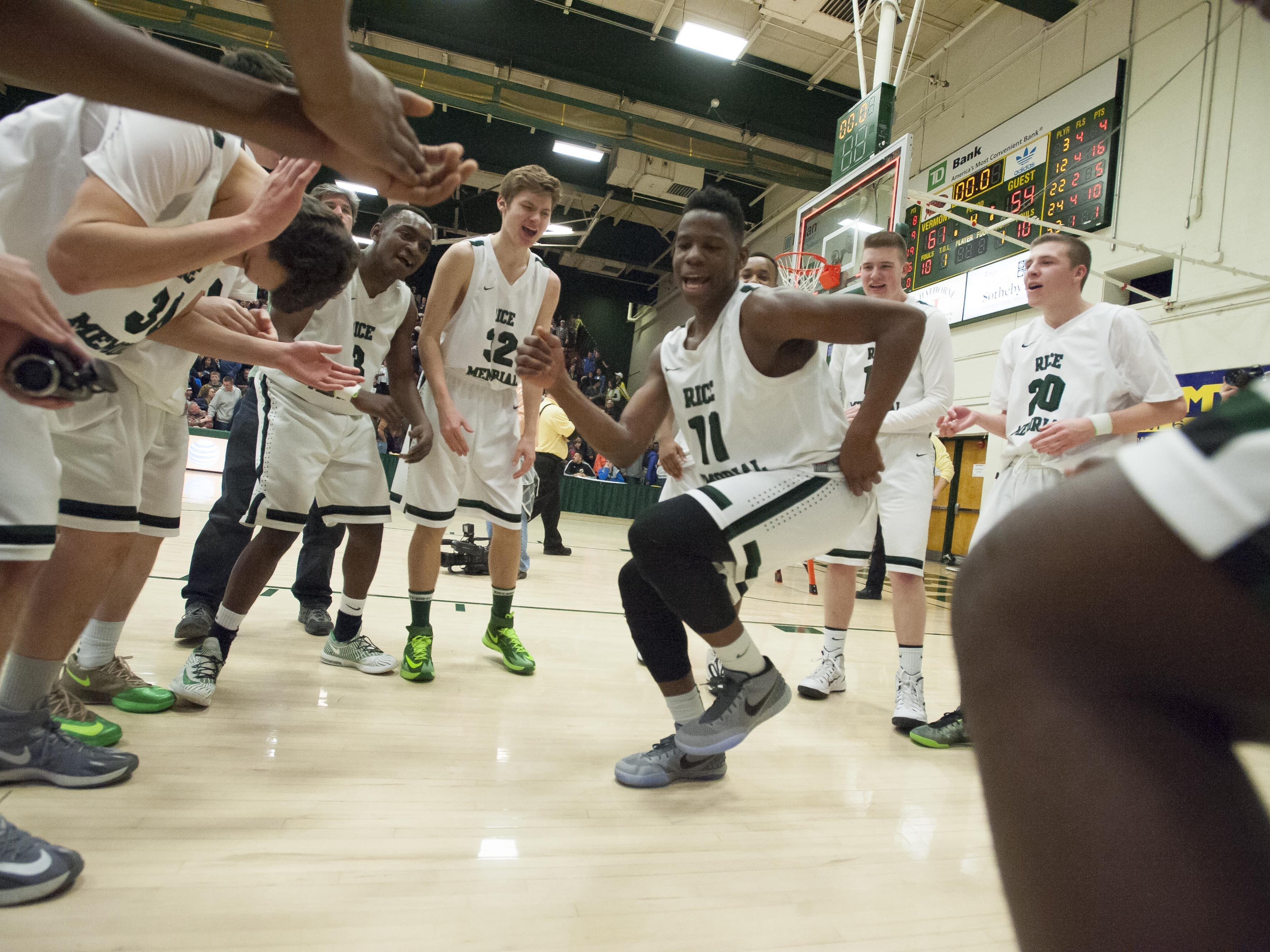 Rice's Ben Shungu dances with his teammates after defeating Burlington during the D-1 boys state basketball championship at Patrick Gymnasium in Burlington on Saturday, March 7, 2015.