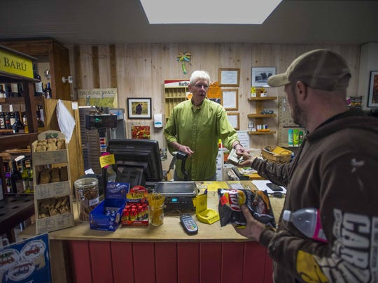Peter Davis rings up a customer at the Underhill Country Store in Underhill Center on in December 2015. In May a co-operative took over management of the store after the Davises announced they wanted to sell the beloved institution and retire.
