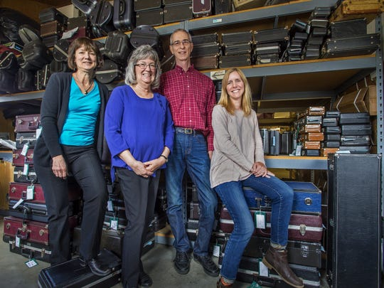 Family members, from left, Ann Greenawalt, Joan Tabor Ellis, David Ellis and Stephanie Fisk seen with some of the many instrument cases at Ellis Music in Bethel this spring.
