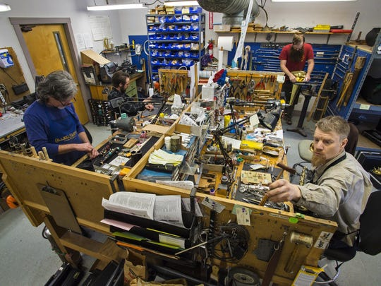 Jonathan Ranney, right, works on repairs at Ellis Music in Bethel this spring. Also working with Ranney are, from left, David Etheridge, Justin Rodig and Gordon Kohl.