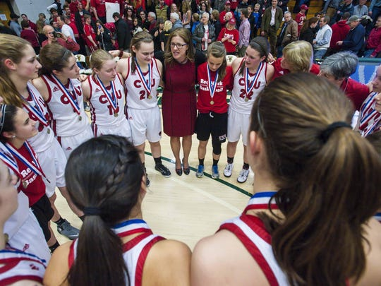 Coach Ute Otley speaks with her team after CVU captured its fourth straight perfect season with the Division I high school girls basketball state title over BFA-St. Albans in March.