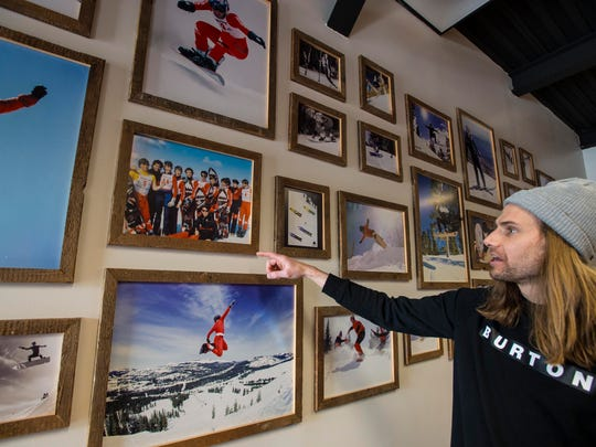 Todd Kohlman, archivist at Burton snowboards in Burlington, gives a tour of the company's historic photos and equipment on Monday.