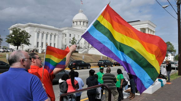 Bruce Britton holds a rainbow flag with the State Capitol in the background. Representatives from several LGBT groups, including Central Alabama Pride in Birmingham and PFLAG of Anniston-Gadsden,  protest against Alabama's immigration law HB56 in front of the State House in Montgomery on Tuesday, March 10, 2015.
