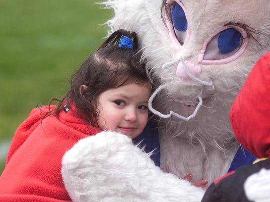 Braving the cold rain Alicia Fresques, 3, of Salt Lake City, gives the Easter Bunny a hug after the Easter Egg Hunt at the Northwest Multi-Purpose Center in Salt Lake City Saturday April 14, 2001.