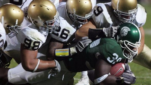 Michigan State's Jehuu Caulrick  is pulled down by a host of tacklers from Notre Dame during the second quarter Saturday Sept. 23, 2006 in East Lansing at Spartan Stadium.