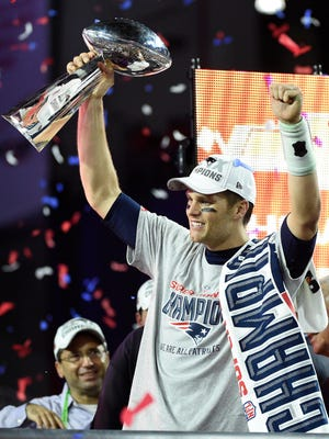 New England Patriots quarterback Tom Brady hoists the Vince Lombardi Trophy after defeating the Seattle Seahawks  in Super Bowl XLIX at University of Phoenix Stadium.