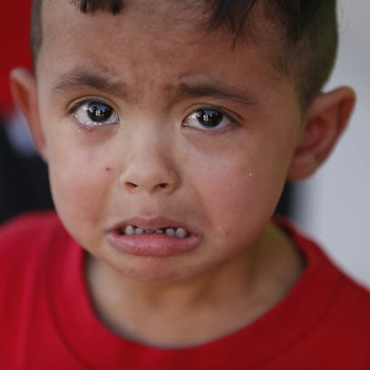 Bryan Rosales, 2, cries during a protest against the