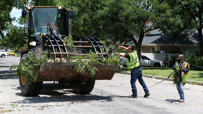 City employees work to clear debris, mostly from damaged trees, scattered across streets throughout San Angelo Saturday, June 24, 2017.