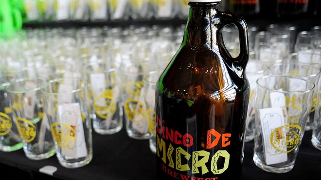 A growler and glasses during Cinco de Micro Brewfest at the Salem Convention Center, on Friday in Salem.