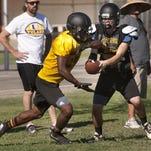 Tulare Union quarterback Josh Guerrero hands the ball off to Romello Harris during an Aug. 10 practice.