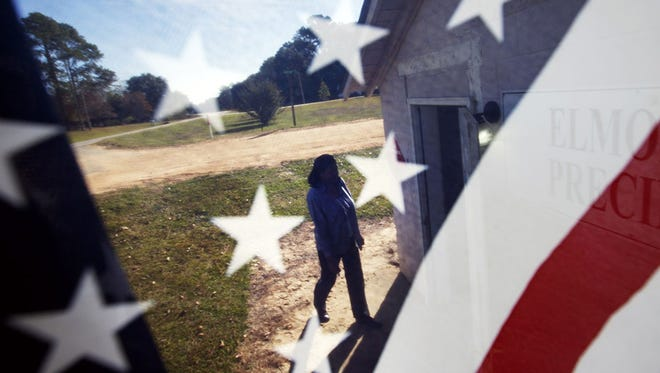 Voter Barbara Hawkins is seen through an American flag as she walks into the Elmodel precinct to cast her ballot in Elmodel, Ga.