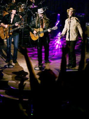 """Willie Nelson, center, performs with Richie Sambora and Jon Bon Jovi during the taping of """"Willie Nelson & Friends — Stars and Guitars"""" at the Ryman Auditorium on April 14, 2002."""