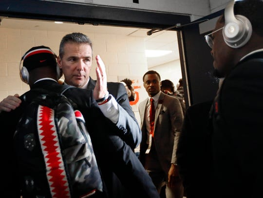 Ohio State coach Urban Meyer greets each of his players